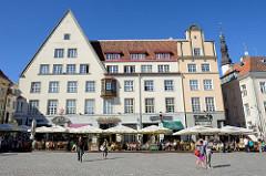 Häuser am  Rathausplatz / Raekoja plats von Tallinn - Restaurants und Cafés in der Sonne, Touristen schlendern über den Marktplatz.