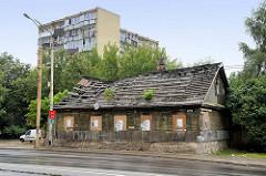 Altes verfallenes Holzhaus mit abgedecktem Dach - mehrstöckiger Wohnblock im Hintergrund; Kauno Straße in Vilnius.