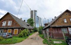 Neu + Alt - ursprüngliche Wohnhäuser / traditionelle Holzbauweise / Holzhaus, schmaler Sandweg - modernes Hochhaus - Stadtteil Šnipiškės in Vilnius.