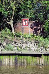 Alte Holzwand / Uferbefestigung am Reiherstieg im Hamburger Hafen. Reste einer Brückenanlage, Ankern verboten Schild.