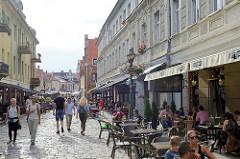 Fussgängerzone / Vilniaus in Kaunas - Touristen schlendern in der Sonne; Aussengastronomie - Restaurants und Cafés, Tische mit Gästen an der Straße.