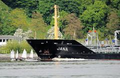 Der Tanker JANA fährt elbabwärts auf der Höhe von Hamburg Blankenese; Kinder lernen das Segeln in Dingis / kleinen Segelbooten neben den fahrenden Grossschiffen. Der Tanker JANA ht eine Länge von knapp 70m und eine Breite von 12m; sein Tankvolumen be