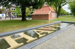Wasserbecken mit Schriftzug HAVEN; Teil des alten Auricher Hafens - im Hintergrund das Pingelhus. Von dort fuhren Früher die Binnenschiffe ab - der Hafenmeister kündigte die Abfahrt durch Schlagen einer Glocke an.