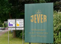 Stadtgrenze zu Jever - Willkommen in der Heimat des Jever Pilsener; Hinweisschilder für Gottesdienste in der Stadtkirche und St. Marien Kirche.