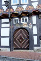 Historische Eingangstür / Wohnhaus in der Rittergasse von Stolberg / Harz. Doppeltür / Farbig abgesetzte dreieckige Türblatt-Verleistung - Türbalken Inschrift Hentz Neugeborn - geschnitzes Innungszeichen der Schlachter / Fleischer, Rinder.