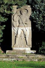 Denkmal von Thomas Müntzer, Steinskulptur - Relief mit Regenbogenfahne der Bauernkriege. Grünanlage / Stadtpark, errichtet 1955.