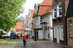 Wohnhäuser am Kirchplatz in Jever, im Hintergrund überragen die Türme der Brauerei die Hausdächer.
