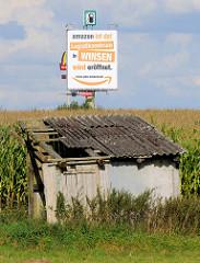 Werbeschild in Bispingen - amazon ist da - Logistikzentrum wird eröffnet, alte verfallene Scheune mit Wellplattendach / Maisfeld.