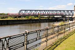 Histrisches rostiges Eisengeländer am Oberhafenkanal  / Billhafen in Hamburg Rothenburgsort; im Hintergrund die Eisenbahnbrücke mit rotem S-Bahnzug.