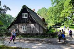Reetdachhaus, Fachwerkgebäude im Dorf von Wilsede / Lüneburger Heide - Straße mit Kopfsteinpflaster, Wegweiser für die unterschiedlichen Wanderwege.