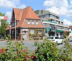 Straßenkreuzung in Schneverdingen - Einzelhaus, Geschäftshaus in Klinkerbauweise - moderner Wohnblock mit Geschäften; Alt + Neu.