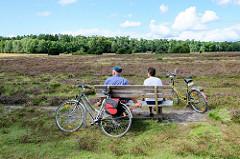 Radtour durch die Lüneburger Heide während der Heideblüte bei Wilsede - Pause auf einer Holzbank.
