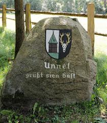 Feldstein  / Findling mit Wappen von Undeloh - niederd. Text Unnel güßt sien Gäst.