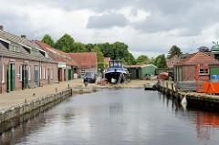 Lagerhäuser, Werkstätten - aufgedocktes Arbeitsschiff im Neuen Hafen von Aurich.