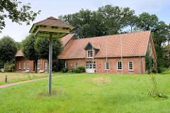 Gebäude der Alfred Toepfer Akademie für Naturschutz in der Lüneburger Heide; im Vordergrund ein Nistturm für Schwalben / Mauersegler.