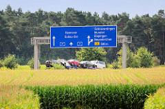 Blick über Maisfelder zur Autobahn A 7 bei Bispingen - Autolaster und Hinweisschild zur nächsten Abfahrt.