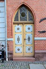 Eingangstür am Gebäude der Alten Post am Marktplatz von Stolberg / Harz. Neogotischer Baustil - Butzenscheiben im Oberlicht, farblich abgesetzte Kassetten mit Schnitzwerk.