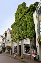Fussgängerzone in Jever - Geschäftshäuser, Läden in der Neuen Straße. Fassade eines Gebäudes dicht mit Efeu bewachsen.