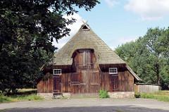 Alte Scheune in der Lüneburger Heide bei Wilsede - mit Reet gedecktes landwirtschaftliches Gebäude, großes Doppeltor .
