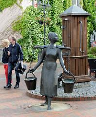 Brunnenanlage ohne Funktion - Küsterspütt 1756 - Wasserträgerin mit Eimern und Trageholz.
