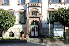 Eingang mit Säulen und verzierter Holztür / Doppeltür mit Eisengitter - Verwaltungsgebäude Landkreis Mansfeld Südharz in Sangerhausen.