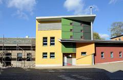 Moderner Neubau mit farbiger geometrischer Fassade, daneben ein graues Wohnhaus mit Baugerüst - Alt + Neu; Architektur in Sangerhausen.