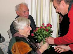 Die Antifaschistin Ester Bejarano bekommt zum 80. Geburtstag einen Strauß roter Rosen überreicht - im Hintergrund der kommunistische Widerstandskämpfer Peter Gingold.
