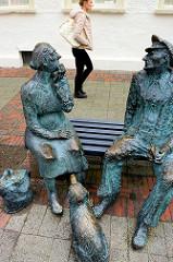 Bronzeskulptur -  sprechendes Paar auf der Bank, sitzender Hund - Fussgängerzone in Aurich; Moorbauernpaar, Bildhauer  Friedrich Büschelberger.