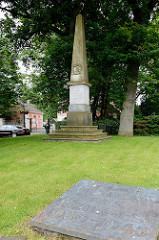 Bronzeplatte - Erinnerung an die Toten des Zweiten Weltkriegs; Entwurf  Hermann Oetken - Einweihung 1962. Im Hintergrund die Stein-Stele zur Erinnerung an die im Kriege gegen Frankreich gefallenen Söhne von Jeverland.
