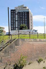 Alte Kaimauer / Ziegelsteinverblendung -  Treppenaufgang mit historischem Eisengeländer am Oberhafenkanal in Hamburg Rothenburgsort - im Hintergrund das Hotel Holiday Inn an den Elbbrücken.