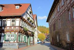 Historisches Fachwerkhaus / Wohnhaus - farbige Rosetten, Blumenkästen, Nutzung als Gaststätte / Am Markt in Stolberg, Harz.