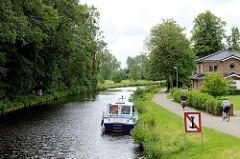 Lauf vom Jade-Ems-Kanal in Aurich - ein Sportboot liegt am Ufer, Schild Ankern verboten - Fahrradfahrter am Leinpfad / Weg entlang des Kanalufers.