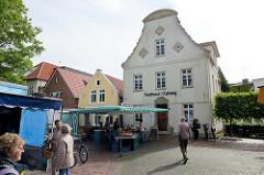Wohnhäuser / Geschäftshäuser am Kirchplatz in Jever, Wochenmarkt / Marktstände.