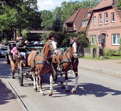 Straßenverkehr in der Hauptstraße von Undeloh in der Lüneburger Heide - Kutsche mit Fahrgästen.