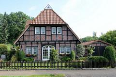 Wohnhaus in Fachwerkbauweise mit Krüppelwalmdach und Fachwerkgarage in Bispingen - Vorgarten mit Rasen und Holzzaun / Staketenzaun