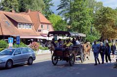 Straßenverkehr in der Hauptstraße von Undeloh in der Lüneburger Heidi - Kutsche mit Fahrgästen, KFZ und Fussgänger.