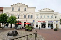 Alter Markt von Jever - historische Häuser und Bronzefigur liegender Bulle. Im Hintergrund das Concerthaus, erbaut 1888 als Gesellschaftshaus - von 1896 bis 1975 Nutzung als Lichtspielhaus, heute Geschäftshaus.