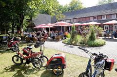 Restaurant, Hotel, Café Schäferhof in der Lüneburger Heide bei Schneverdingen - geparkte Fahrräder, Tische unter Sonnenschirmen.