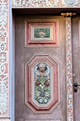 Schmucktür mit aufwändigen Schnitzerein und Blumenschmuck in der Jüdenstraße von Duderstadt.