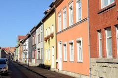 Einstöckige Wohnhäuser mit unterschiedlich farbigen Fassaden in der Grünstraße von Mühlhausen.