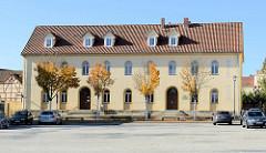 Freier Platz am Mühlhäuser Blobach, Nutzung als Parkplatz und Rummelplatz, fast symmetrisches Gewerbegebäude.