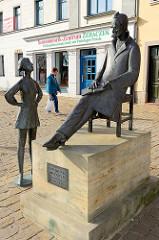 Bronzeskulptur von Friedrich Nietzsche am Holzmarkt in Naumburg; eingeweiht 2007, Bildhauer Heinrich Apel.  im Hintergrund ein Zentrum für Sensomotorik, Geschäft für Orthopädieschuhtechnik mit Podologie-Praxis.