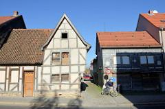 Altes leer stehendes Fachwerkhaus mit verrammelten Fenstern in der Johannesstraße von Mühlhausen; daneben ein ebenso verlassenes Wohnhaus mit Schiefer Schindelfassade.