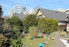 Einzelhäuser mit Satteldach und Vorgarten mit Kinderspielzeug - im Hintergrund Hochhäuser und Wohnblocks; Wohnstraße in Norderstedt.