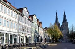 Geschäftshäuser, Café mit Aussengastronomie - historische Altstadt von Duderstadt, Marktstraße mit Kopfsteinpflaster. Im Hintergrund die römisch-katholische Basilika St. Cyriakus / Probsteikirche.