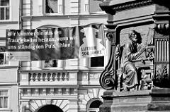 Sockel vom Luther Denkmal in Eisenach, Darstellung Lutter in der Studierstube auf der Wartburg; im Hintergrund ein Transparent mit dem Luther-Text: wir kommen nie aus den Traurigkeiten heraus, wenn wir uns ständig den Puls fühlen.