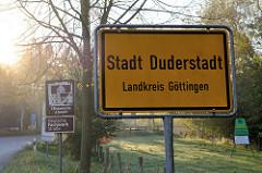 Ortsschild Stadt Duderstadt, Landkreis Göttingen - im Hintergrund Hinweisschild auf Historische Altstadt und Deutsche Fachwerk Straße.
