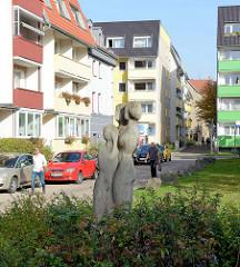 Moderne Wohnblocks mit farbig gestalteten Balkons in der Hützelsgasse von Gotha; Steinskulpturen drei Frauen / Mädchen im Gebüsch.