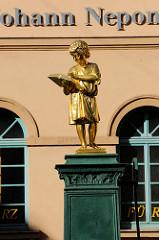 Figur des Bürgerschulbrunnens an der Bürgerschule in Weimar, vergoldete Figur eines lesenden Knaben aufgestellt (Knabe mit Evangelium); aufgestellt 1858 - Entwurf Carl Georg Kirchner.