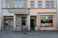 Alt + Neu, leer stehendes Lebensmittelgeschäft mit verfallener Hausfassade, daneben ein restauriertes Gebäude mit dem Al Capone Pizzaservice in der Neustraße von Naumburg.
